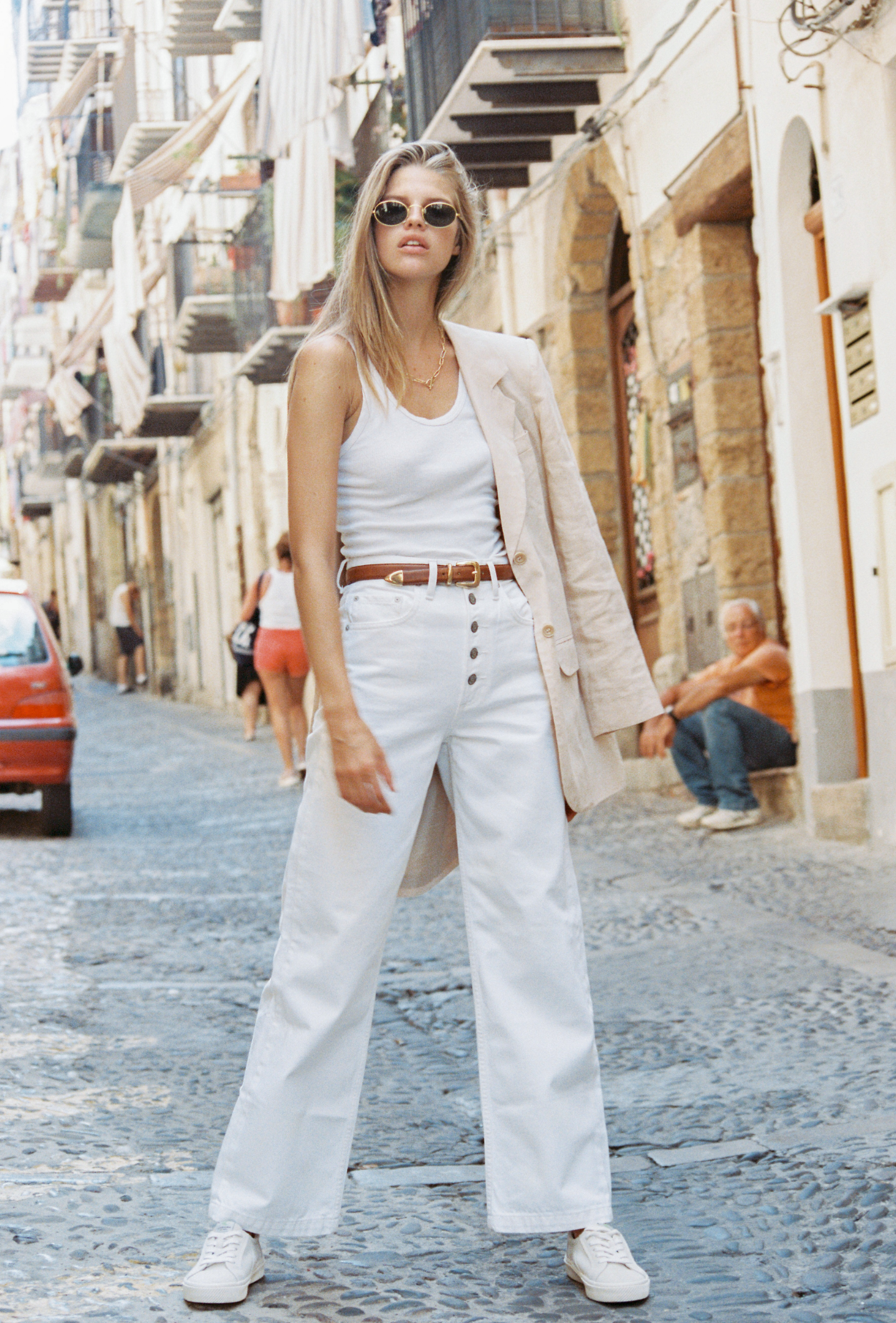 woman standing on a street modelling white jeans