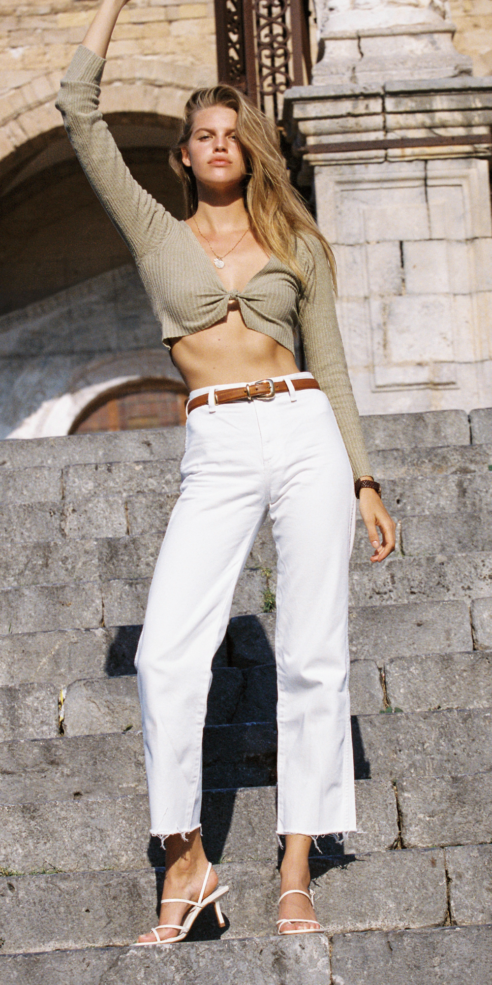 woman standing on stone steps in white jeans