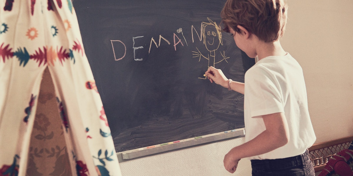 Child writing Demain on charcoal board