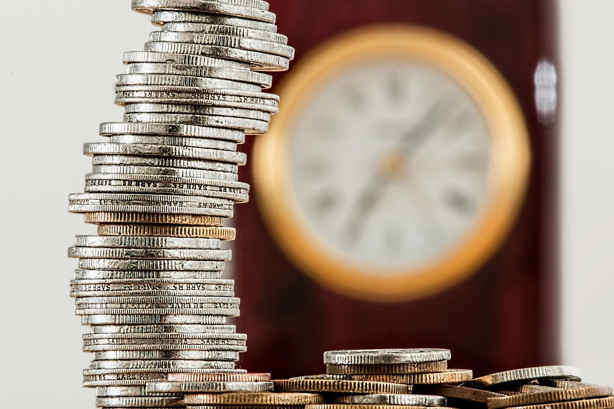gold and silver coins stacked up with a clock in the background