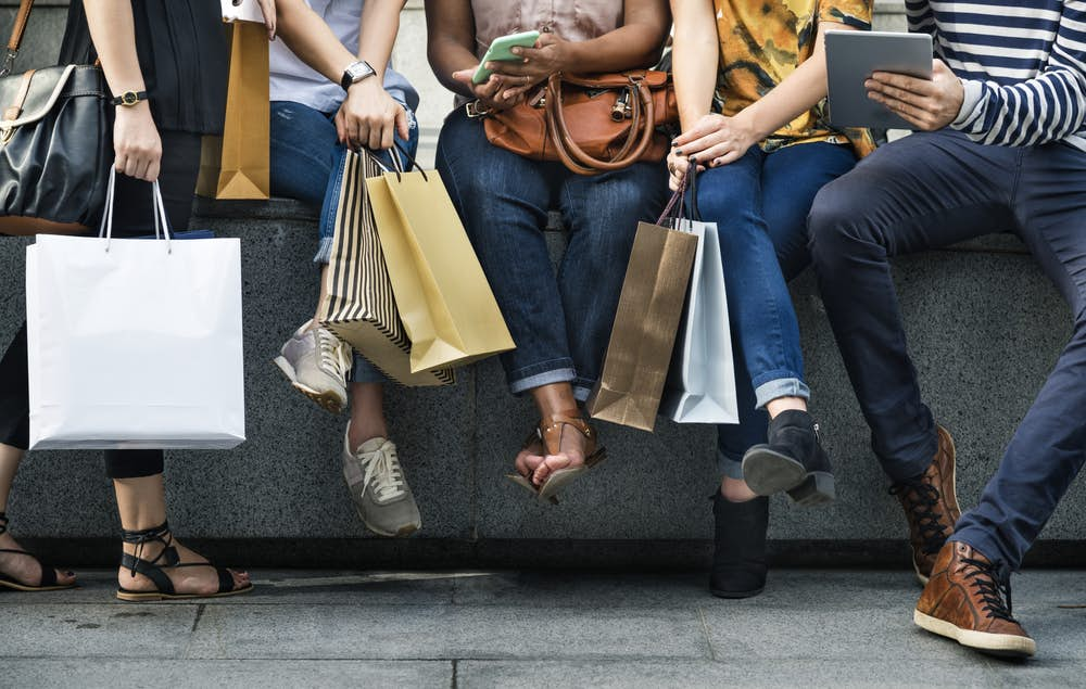 Five shoppers sitting together looking at their phones to trace tracing their purchases