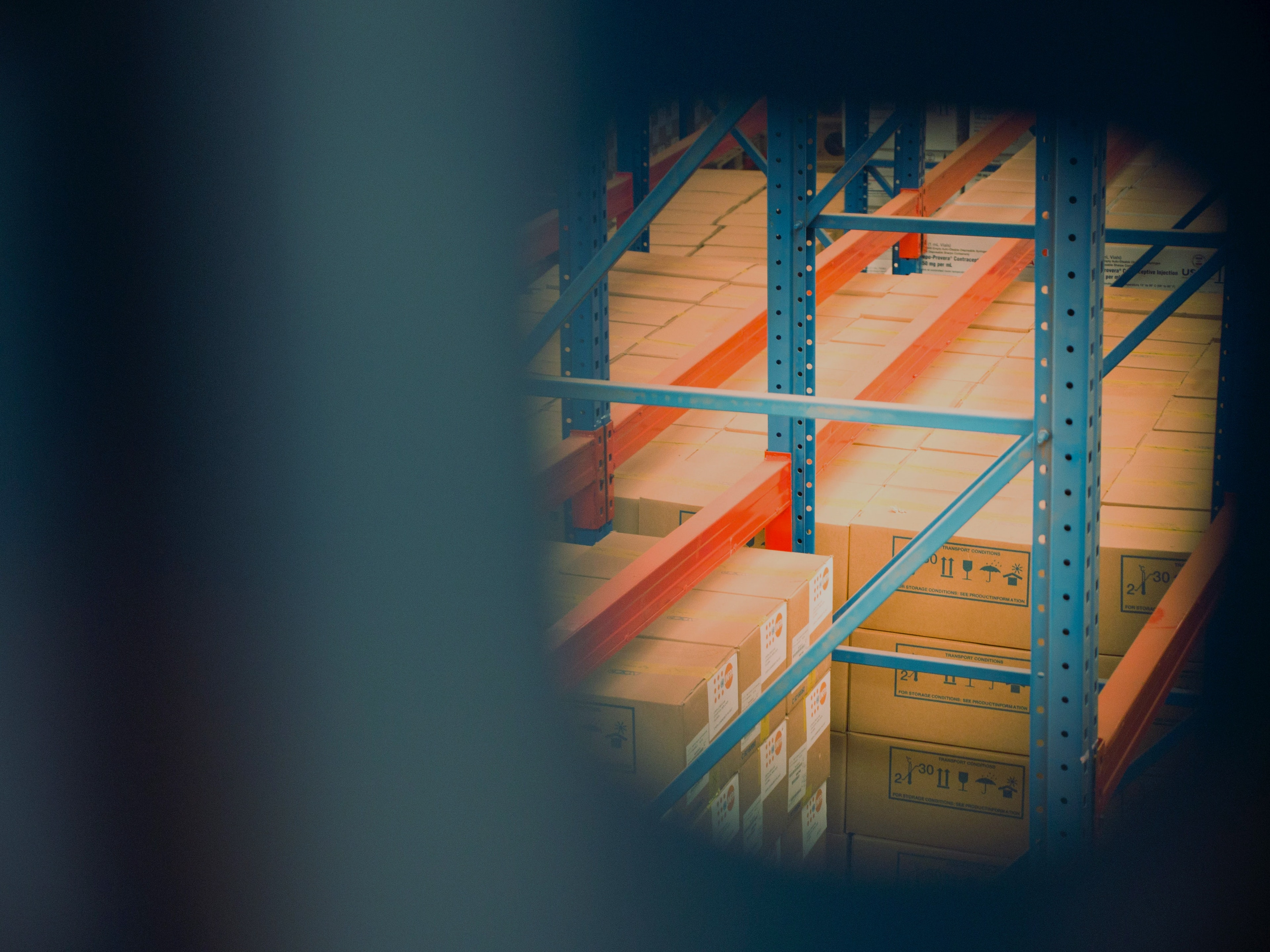 narrow key hole view of supply boxes in a warehouse