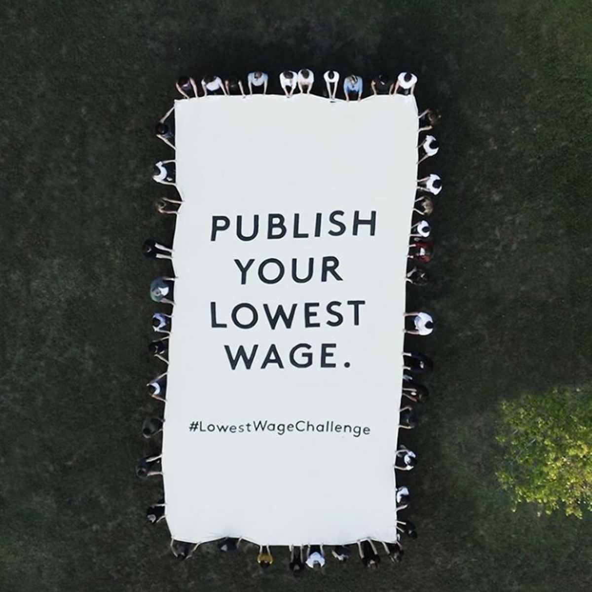 """Bird's view of people holding a large sheet that says """"Publish your lowest wage. #LowestWageChallenge"""""""