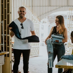 Outland Denim employess holding denim clothes and laughing