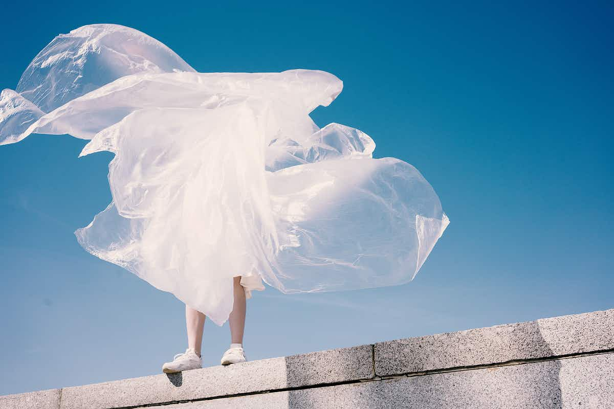 Person standing on ledge holding clear plastic sheet in the wind