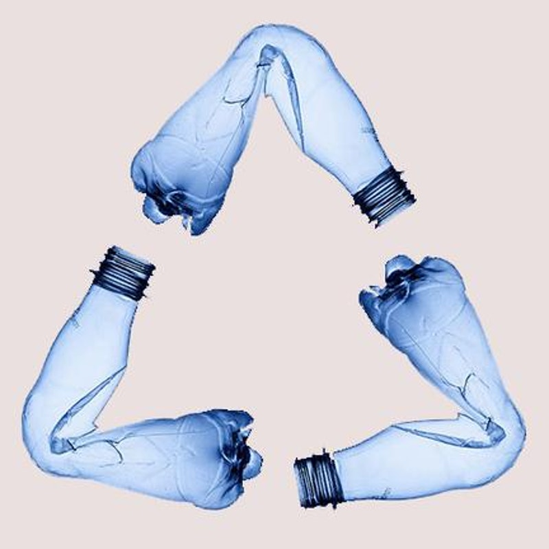 three plastic bottles arranged in a way to visualize the green recycling logo
