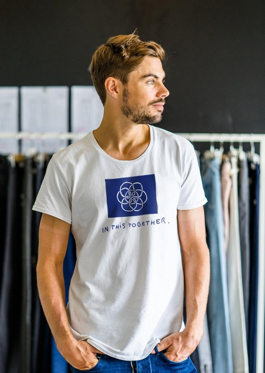DAWN DENIM employee Marian standing with hands in pockets and white t-shirt looking to the right