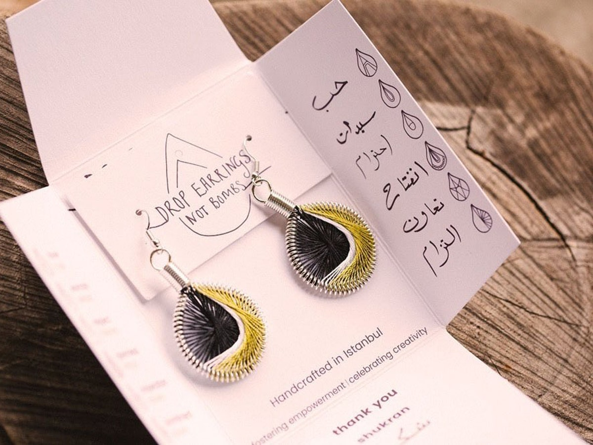 One of the Drop Earrings not Bombs design in packaging with Arabic scripture