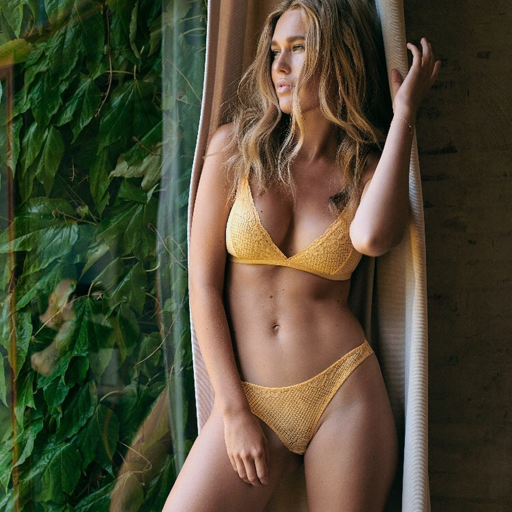 Woman posing in yellow recycled polyester lingerie