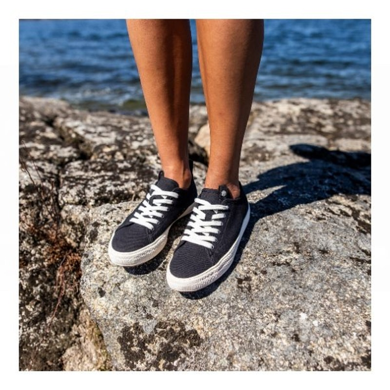 Person wearing dark grey sneakers standing on rock before the sea